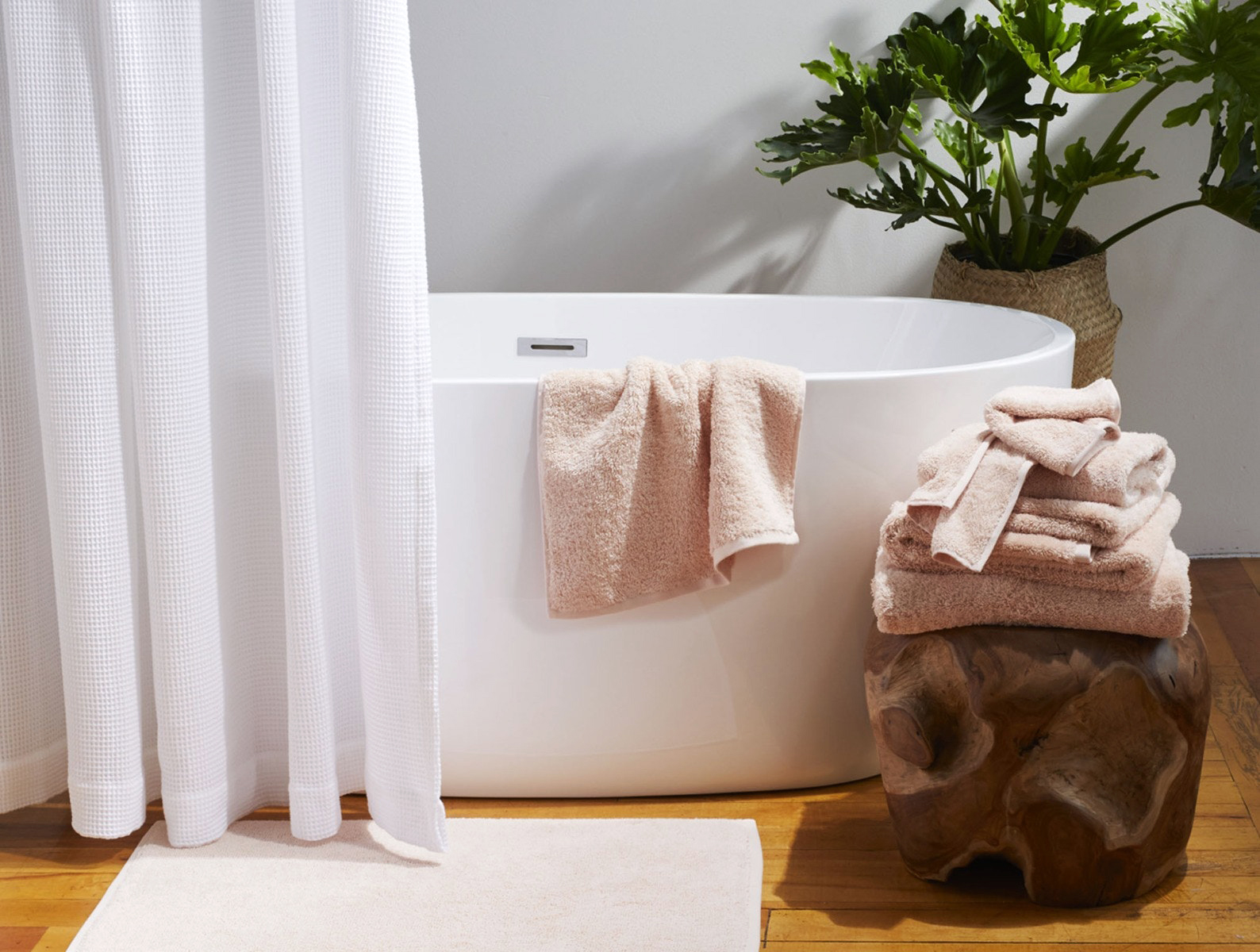 neutral towels by a white soaking tub