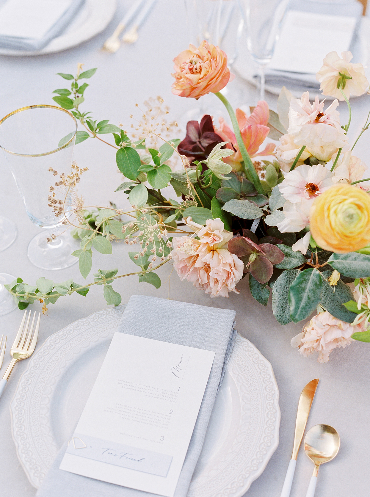thuy kahn wedding place setting white plate floral centerpiece