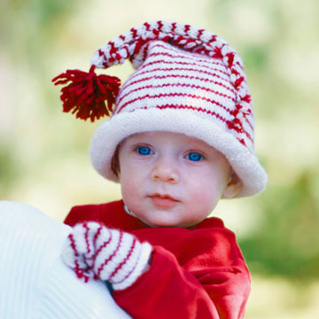 Baby in red and white knit cap with pom pom