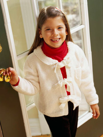 Young girl wearing white tied knit sweater
