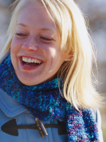 Close up of woman wearing a blue knitted scarf