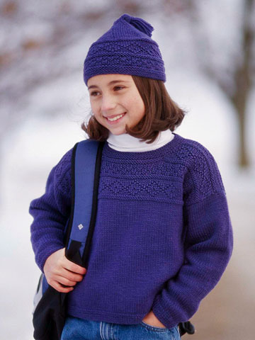 Young girl wearing blue knit sweater and cap