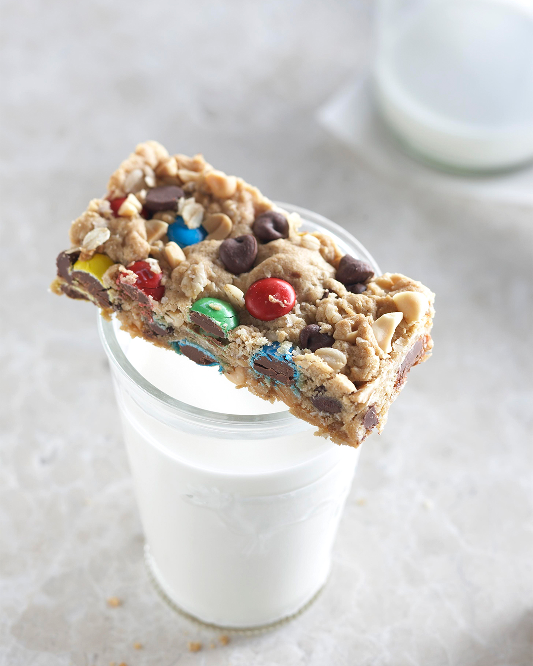 Easy Monster Cookie Bar sitting on top of glass of milk