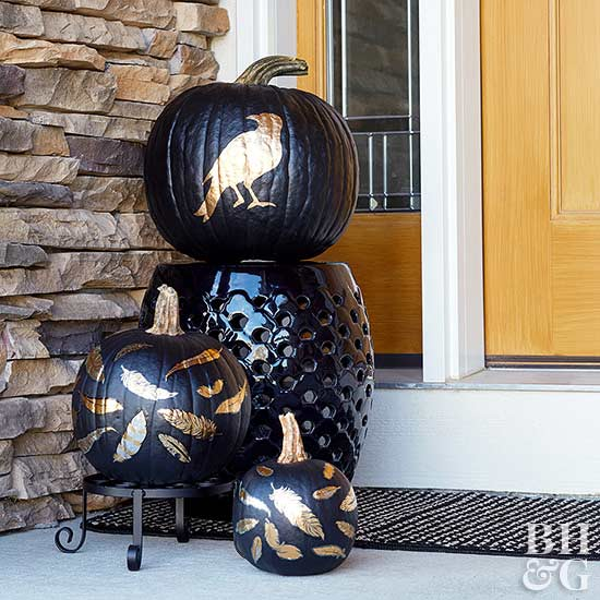 three black pumpkins with gold painted feathers and crow by front door