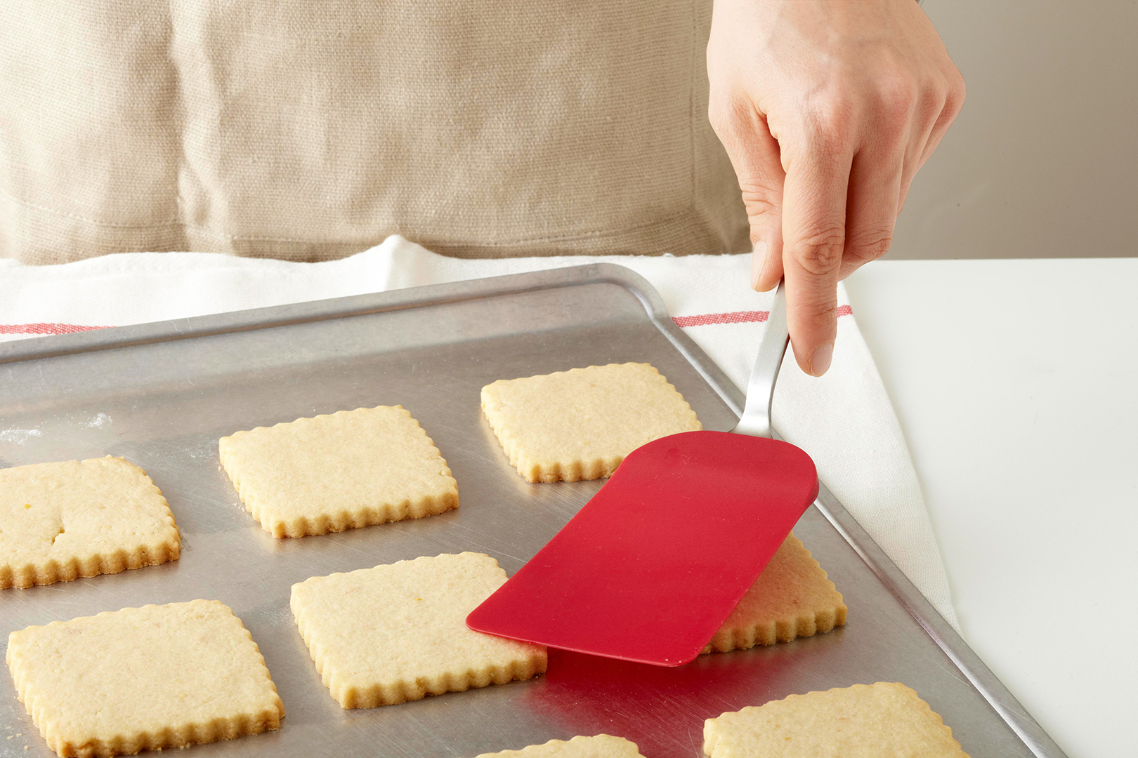 Testing square sugar cookies with spatula test on cookie sheet