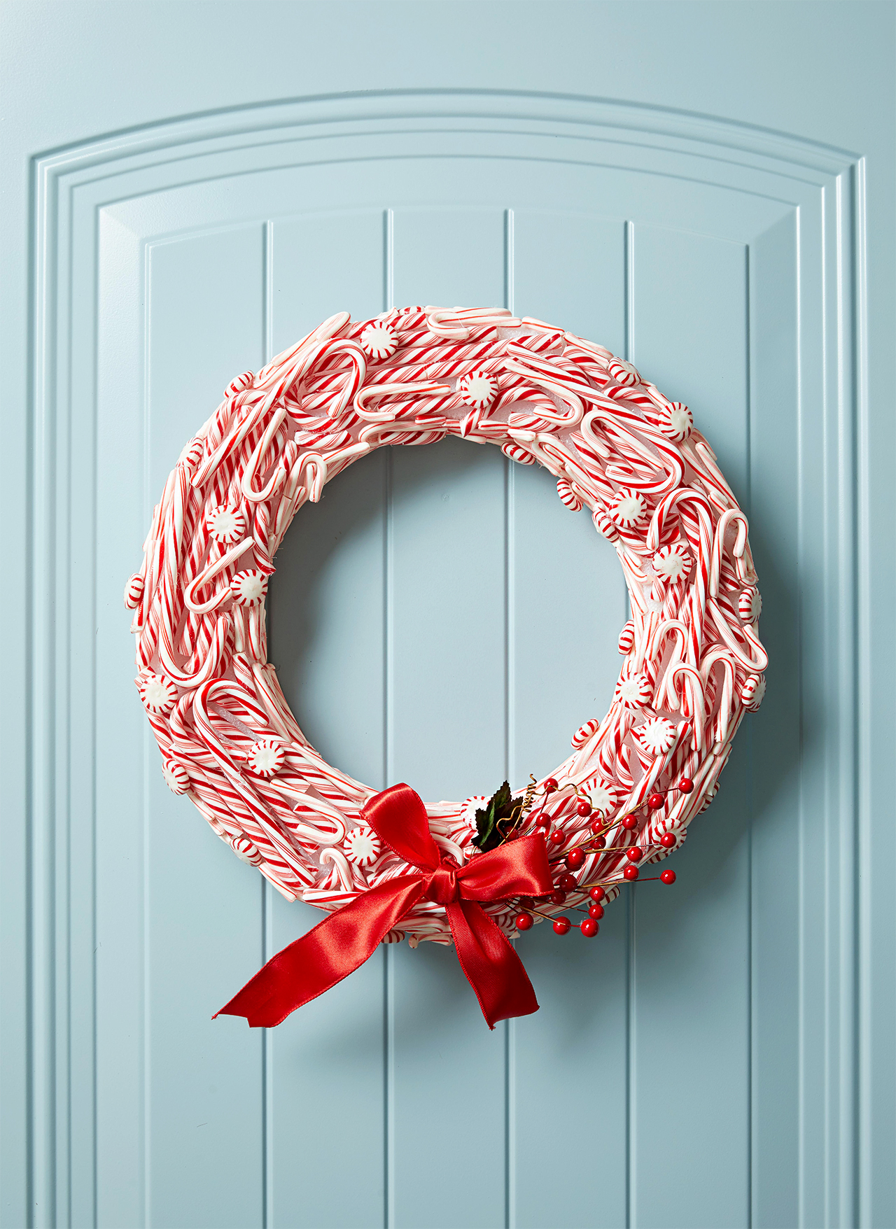 hanging red and white wreath with peppermint candies
