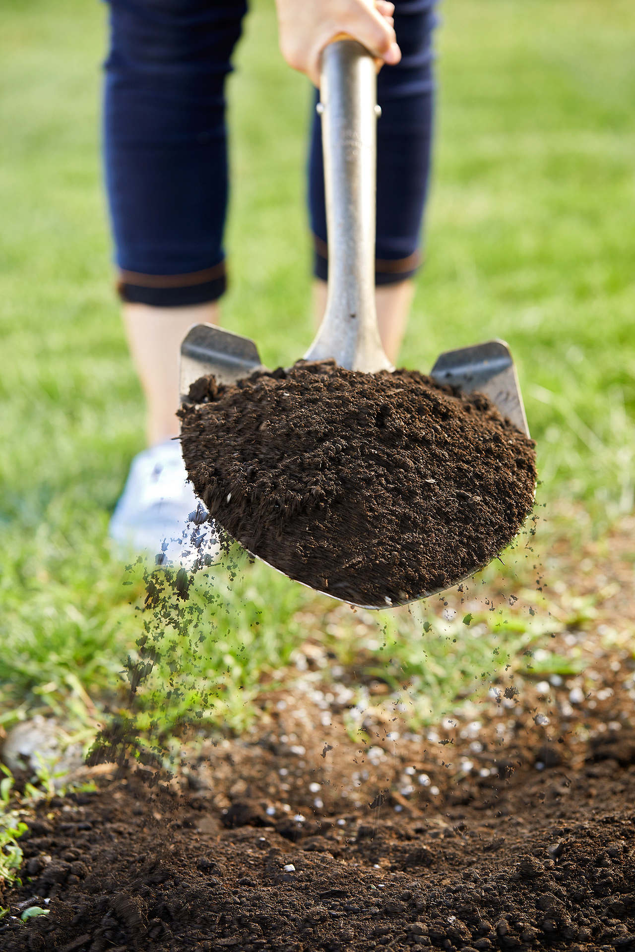 woman scooping soil with shovel