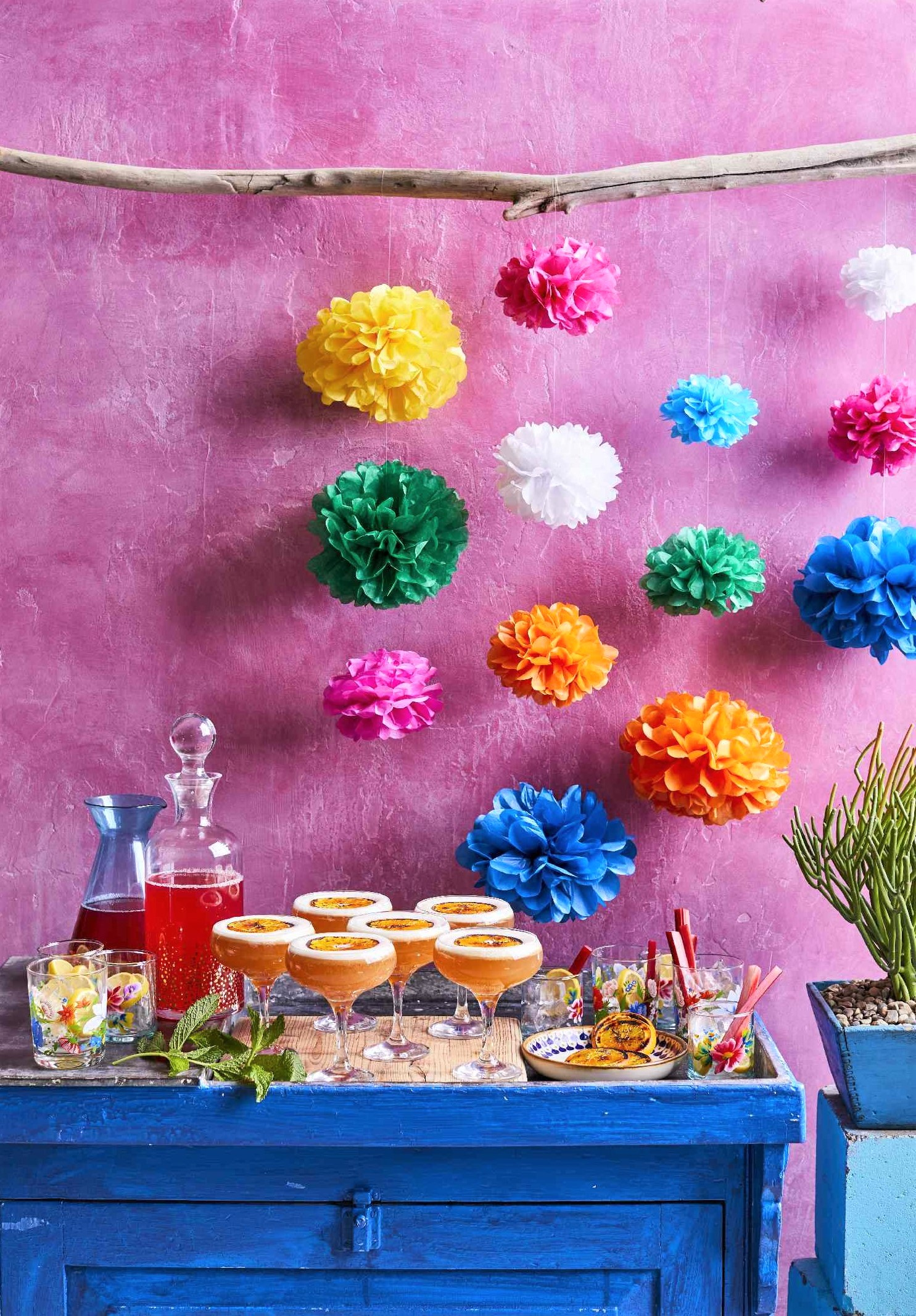 Food and drinks on a table in front of pink wall that has tissue poms hanging over it