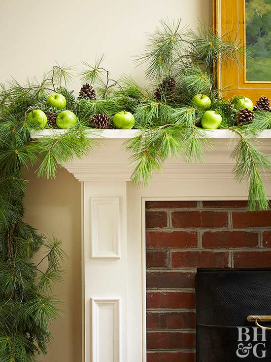 holiday mantel with green apples and and pinecones