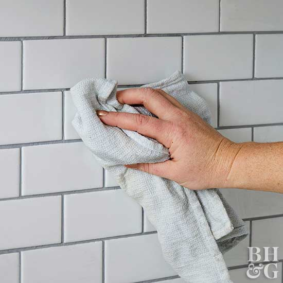 wiping tile and grout with rag