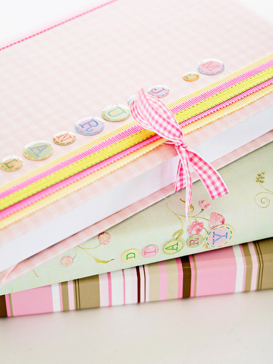 Three notebooks covered with scrapbooking supplies, embellishments and ribbon