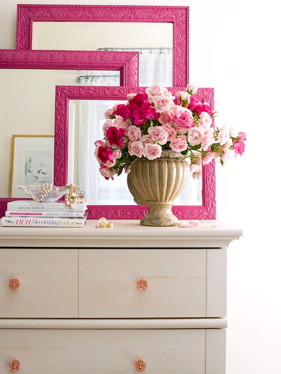 Pink mirrors and frames on dresser,