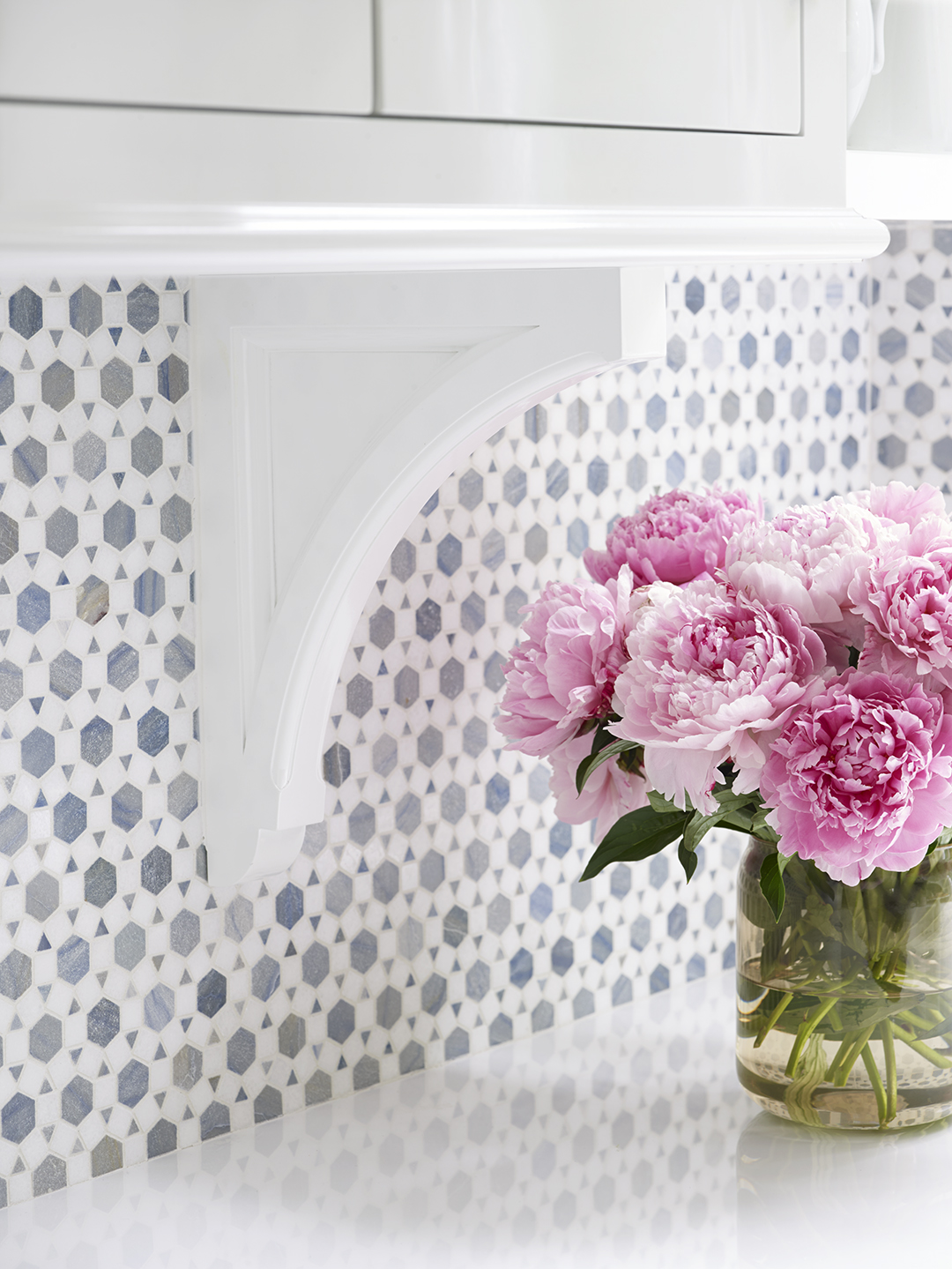 geometric backsplash and vase of peopnies