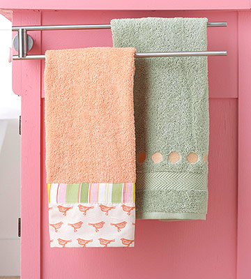 Embellished hand towels hanging from rod