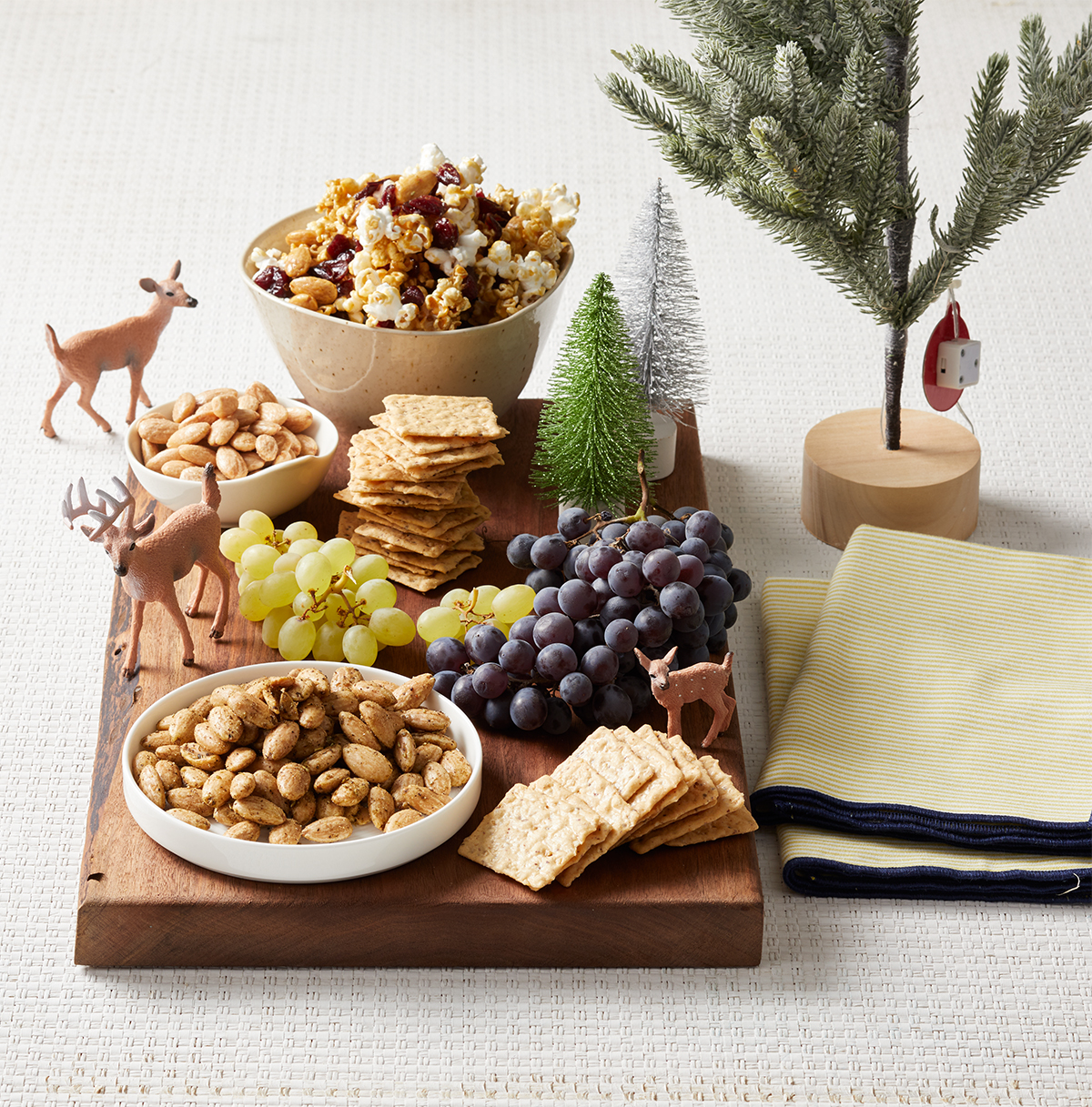 wooden board with grapes crackers snack mix and deer figures and trees