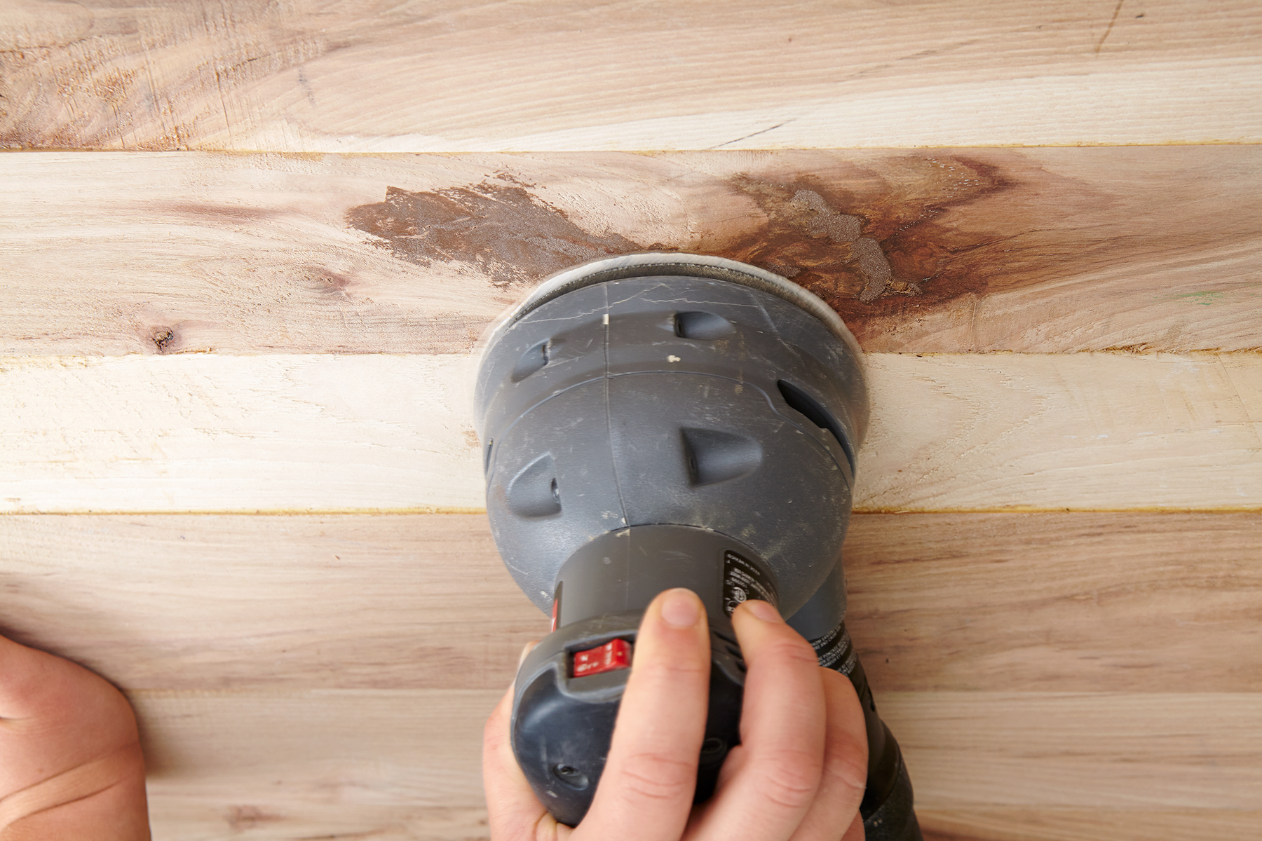 person using rotary sander on wood