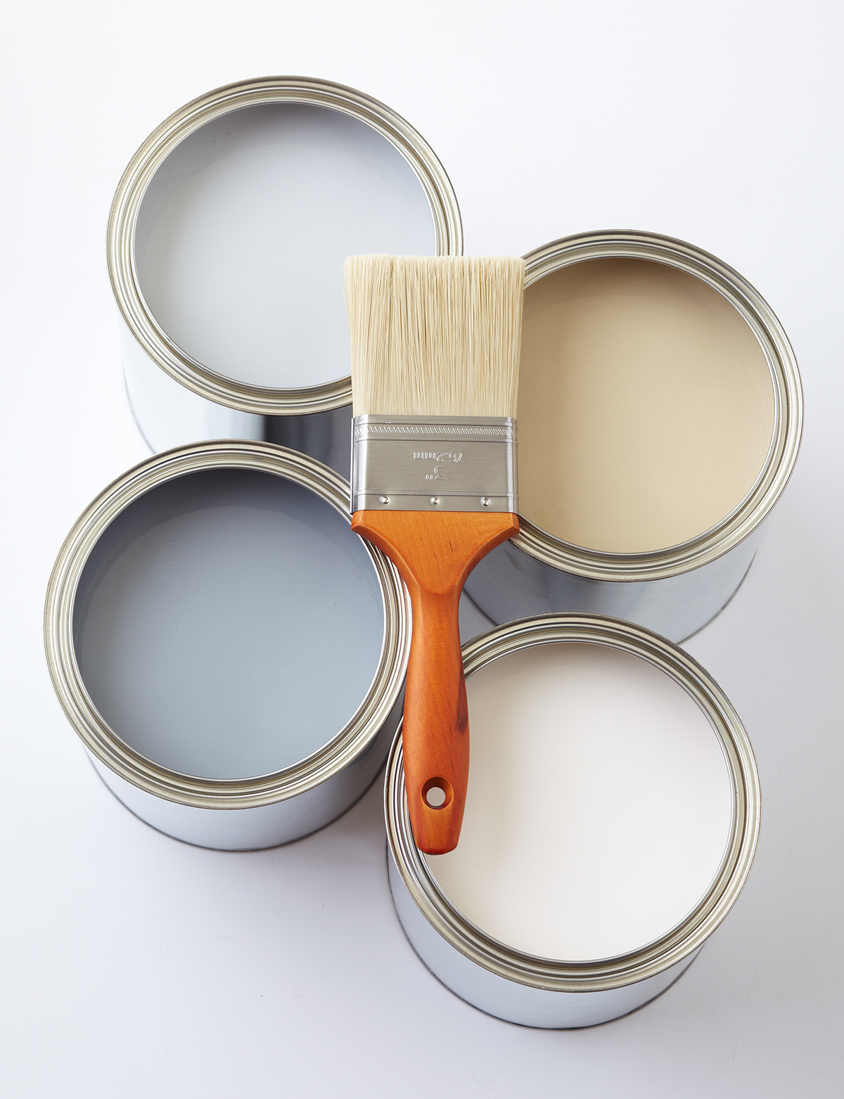 four open paint cans with paintbrush on top