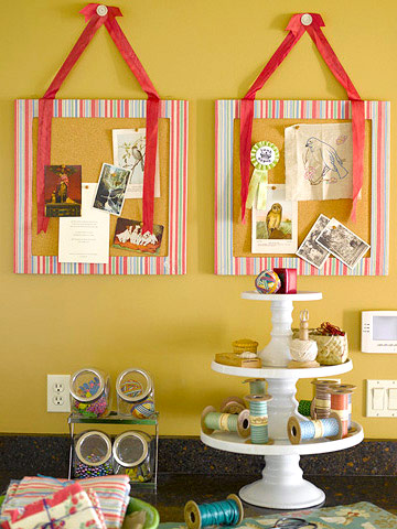 Pink striped corkboards hang above a work space with three-tier cake stands