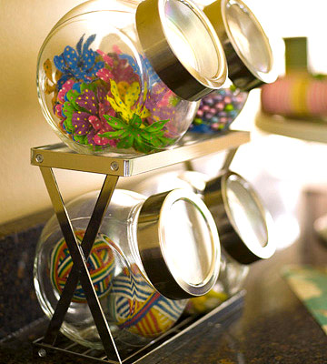 Glass jars with silver lids, filled with art supplies, set on a countertop shelf