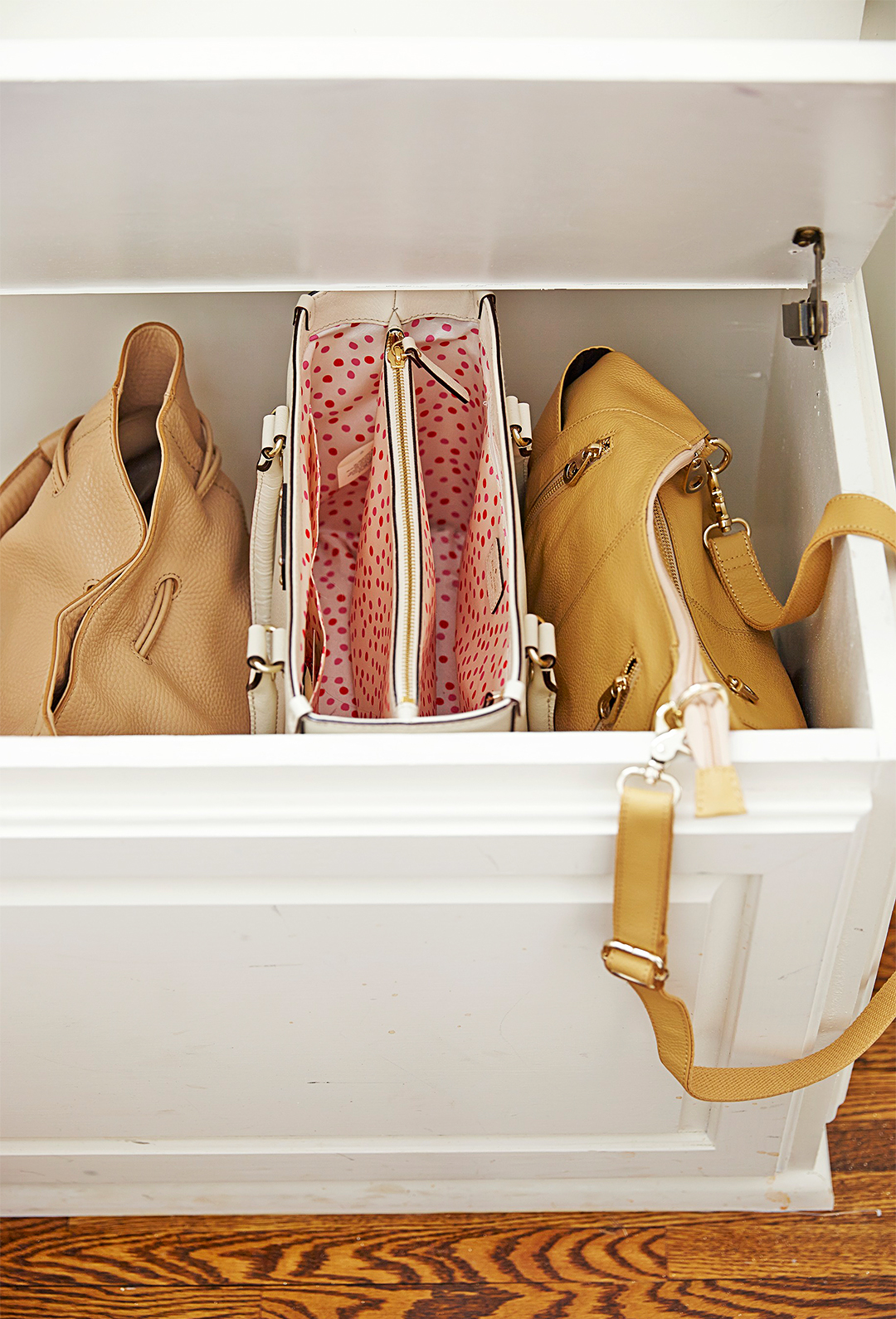 white storage bench with purses inside functional organization