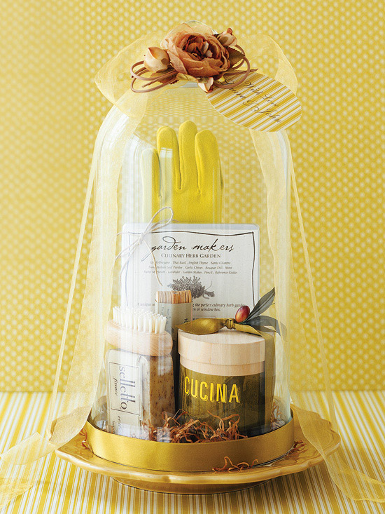 Gardening supplies arranged inside glass cloche with ribbon
