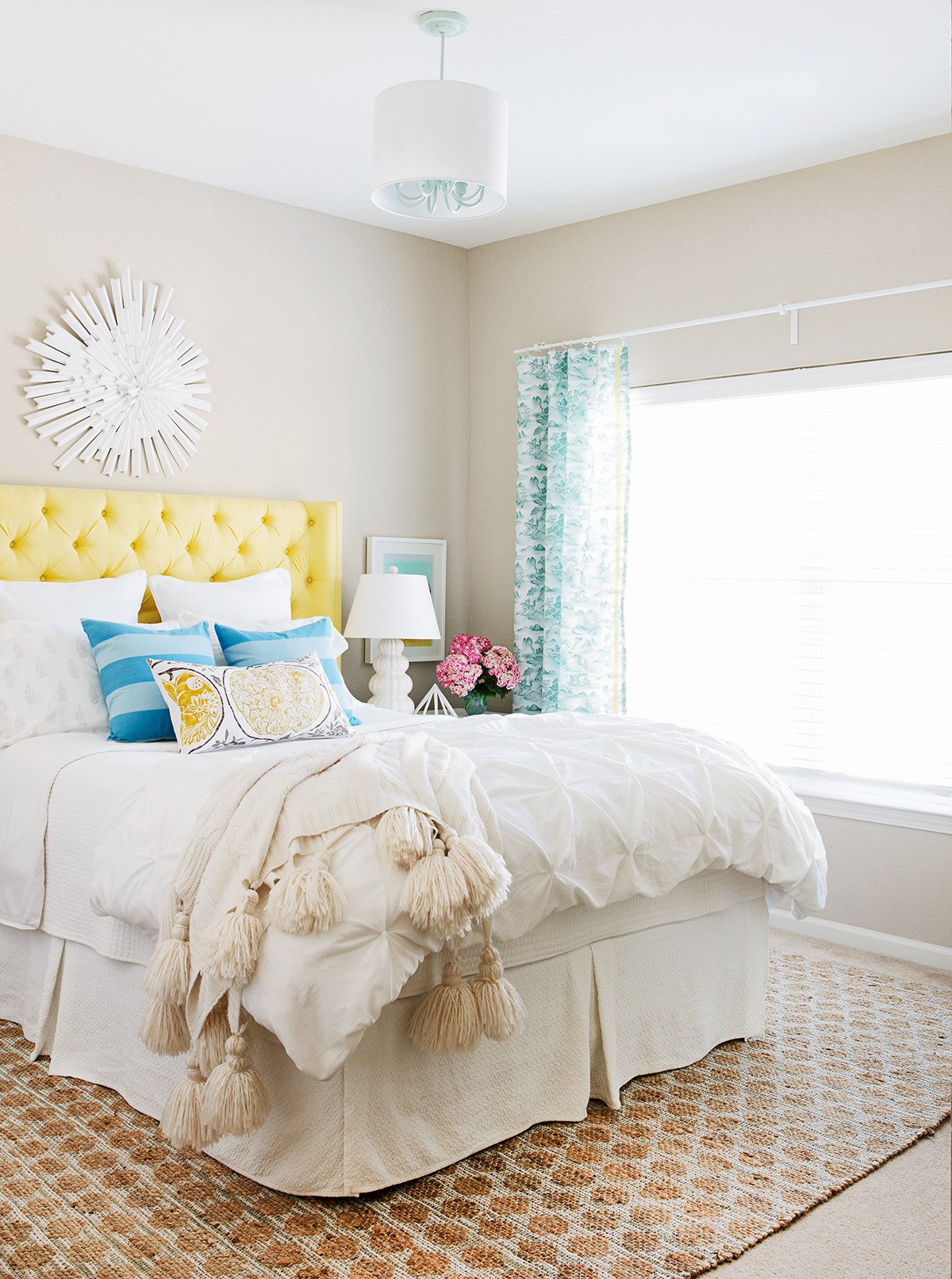 bedroom yellow upholstered headboard sunburst mirror