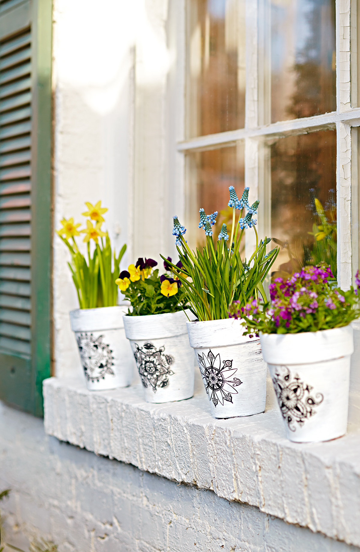 four diy white terra-cotta pots with graphic transferred designs