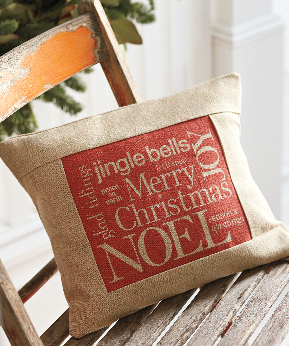 beige throw pillow decorated with red iron-paper with Christmas words