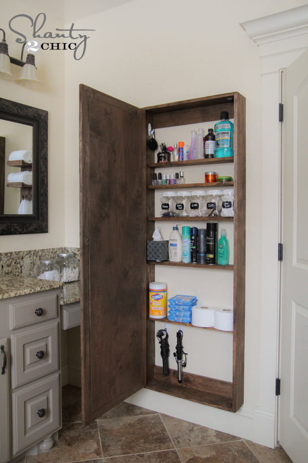 mirror cabinet open to show toiletries in bathroom