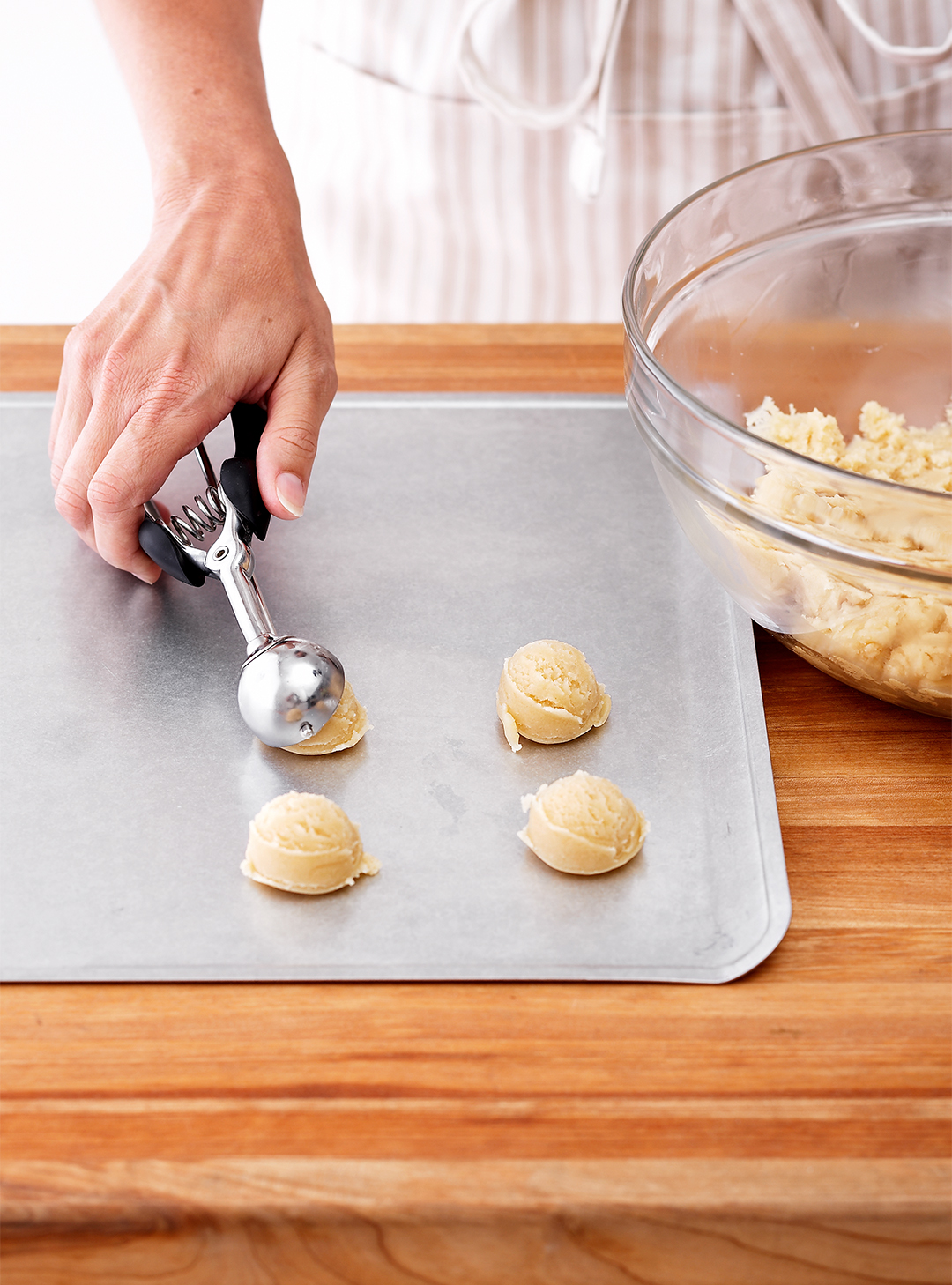 Scooping sugar cookie dough onto baking sheet pan glass bowl woman