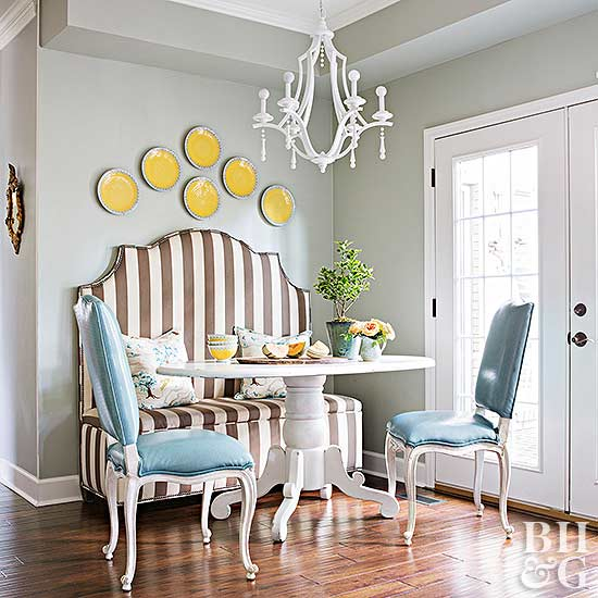 Chandelier hanging over dining table and striped banquette with yellow plates on wall