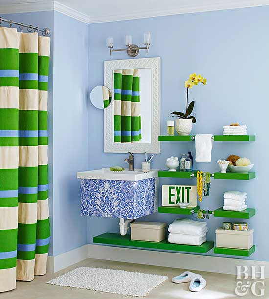 bathroom with light blue walls and bright green open shelving and green and blue stripped shower curtain