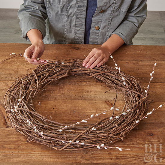 Applying pussy willow to wreath