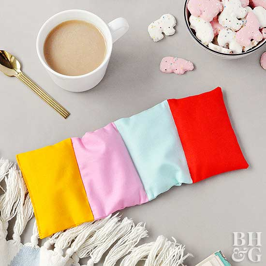 colorblock heating pad with warm cup of tea and cookies