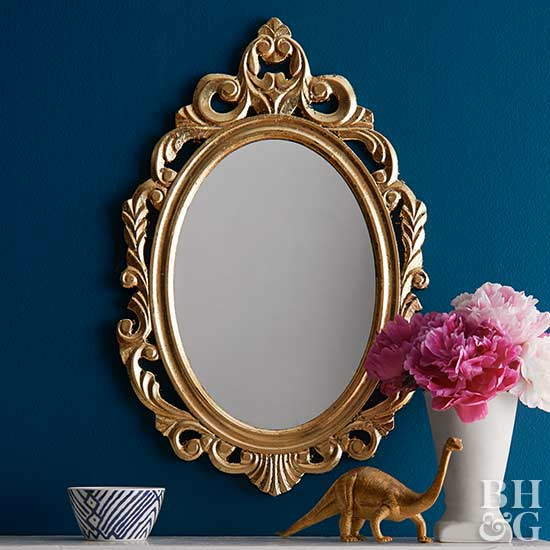 white mantle with gold mirror above and gold knickknacks