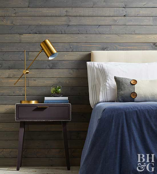 bedroom with nightstand, wall, pillows, lamp