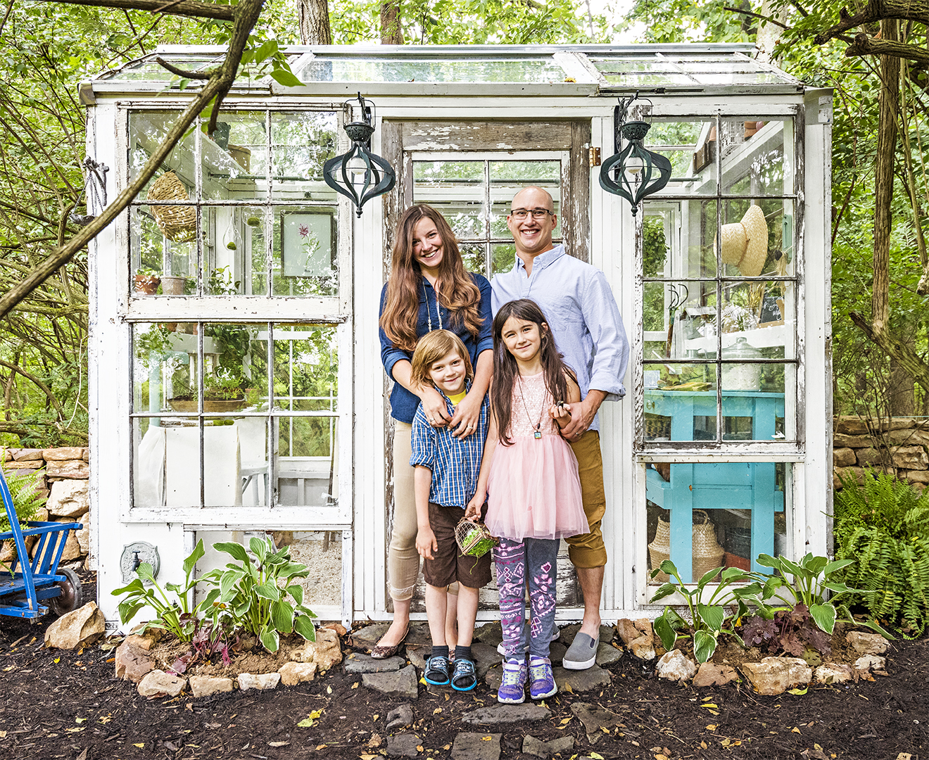 family posing in front of greenhouse