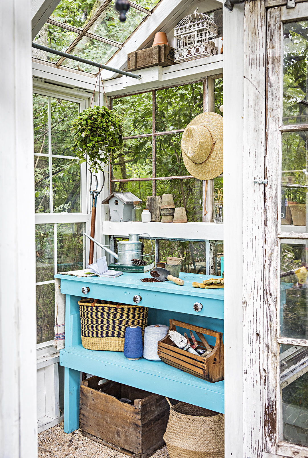 blue potting bench in vintage glass greenhouse