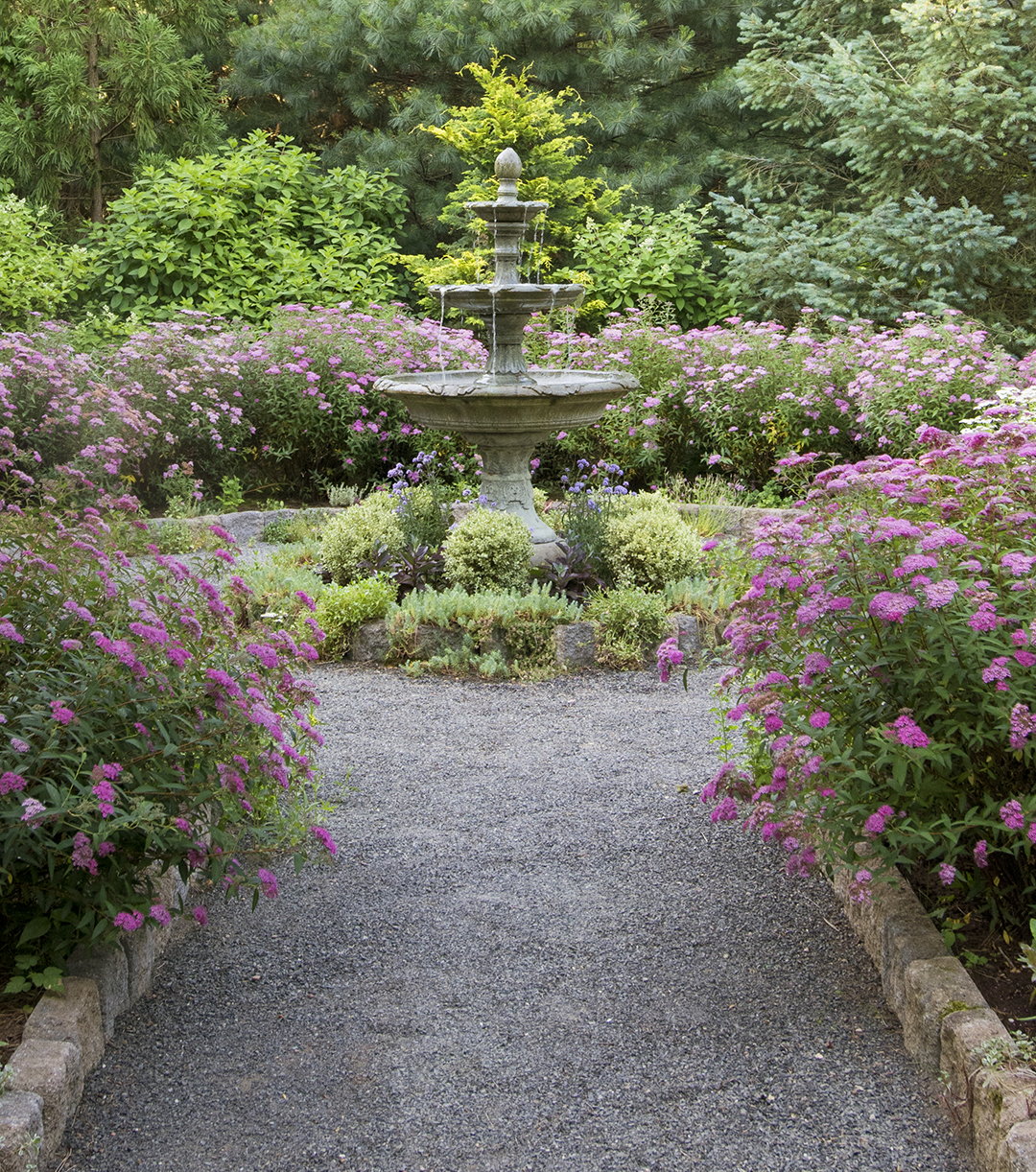 stone path and tiered fountain in formal garden
