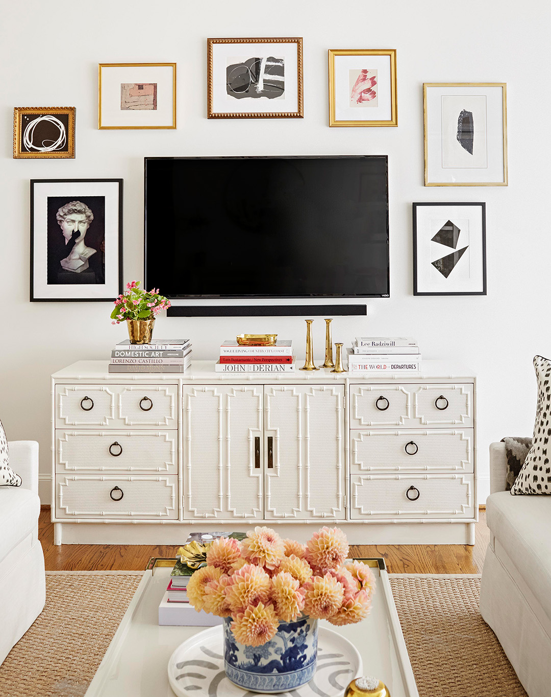 gallery wall with flatscreen tv above vintage Hollywood Regency credenza