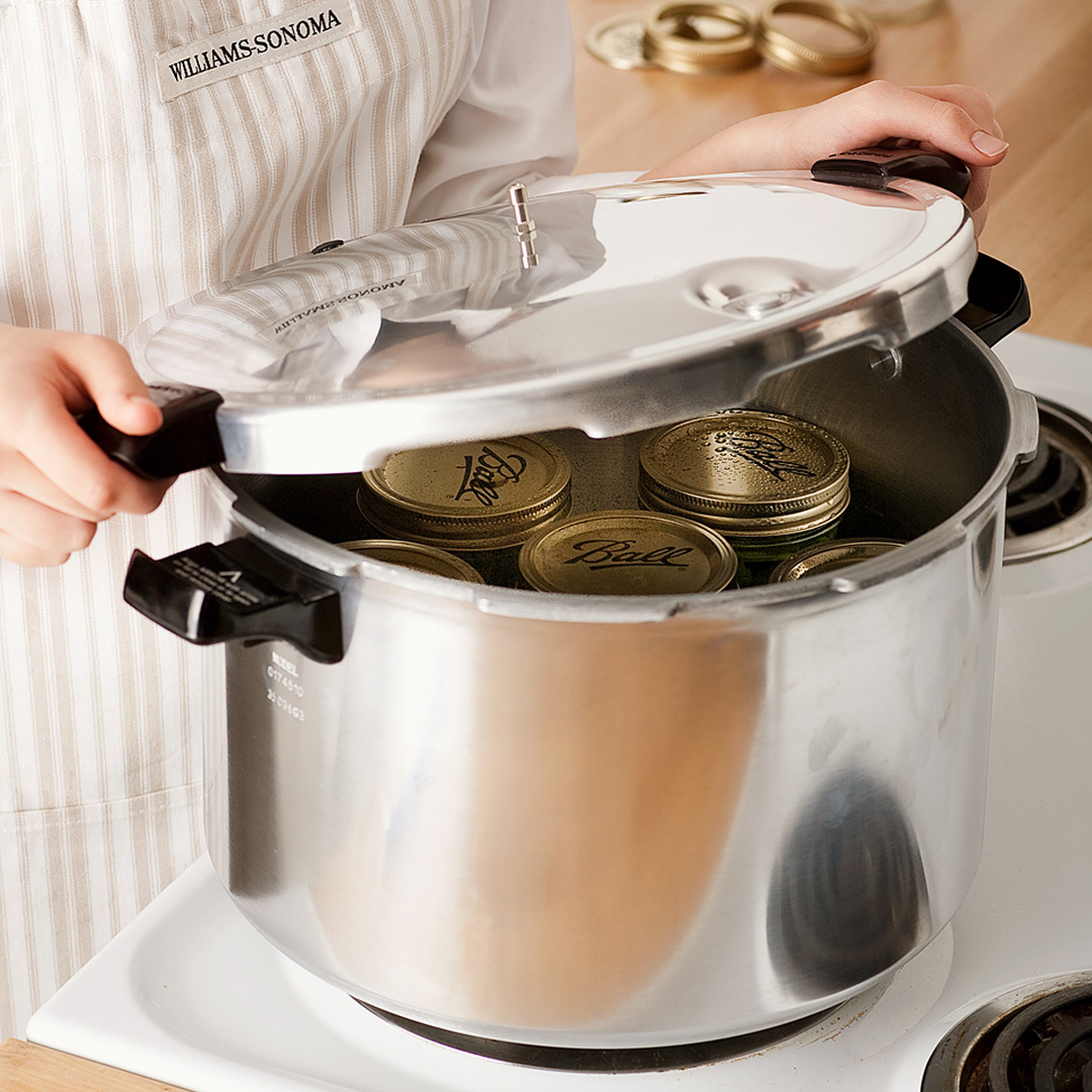 pressure cooker on stove with glass jar cans inside