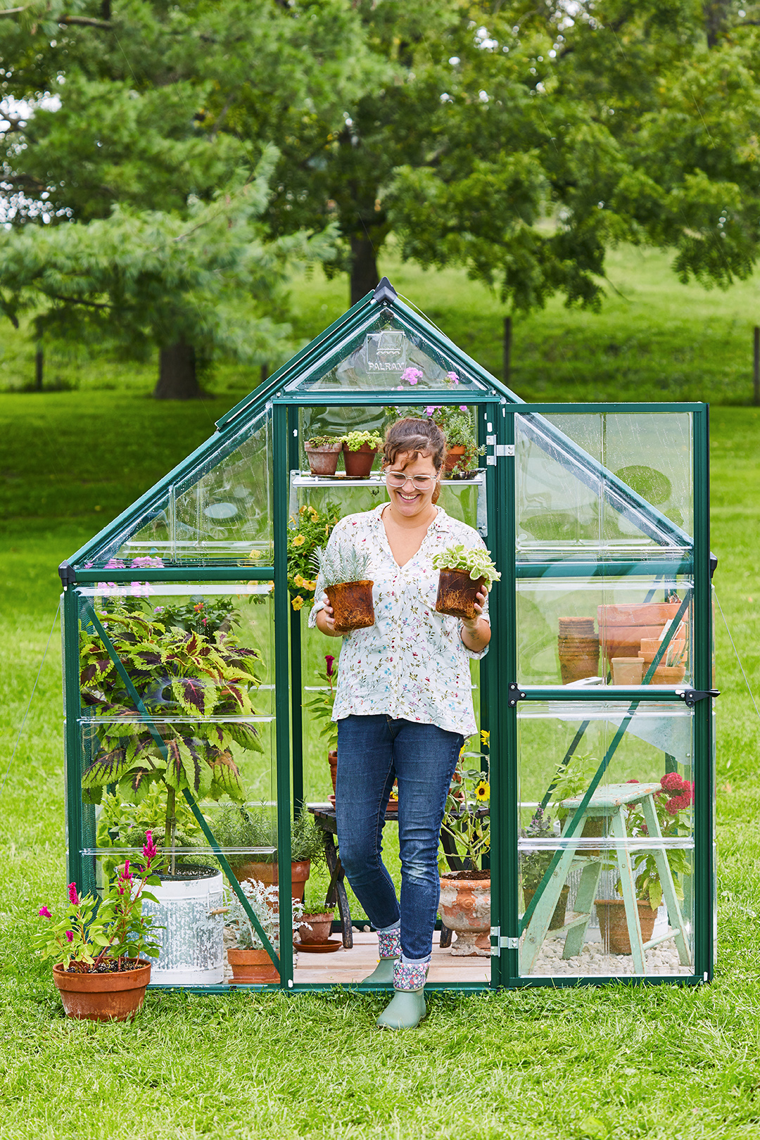 woman carrying two plants from greenhouse