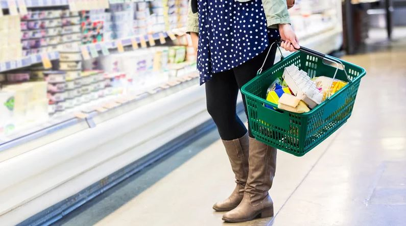 Woman grocery shopping with full basket