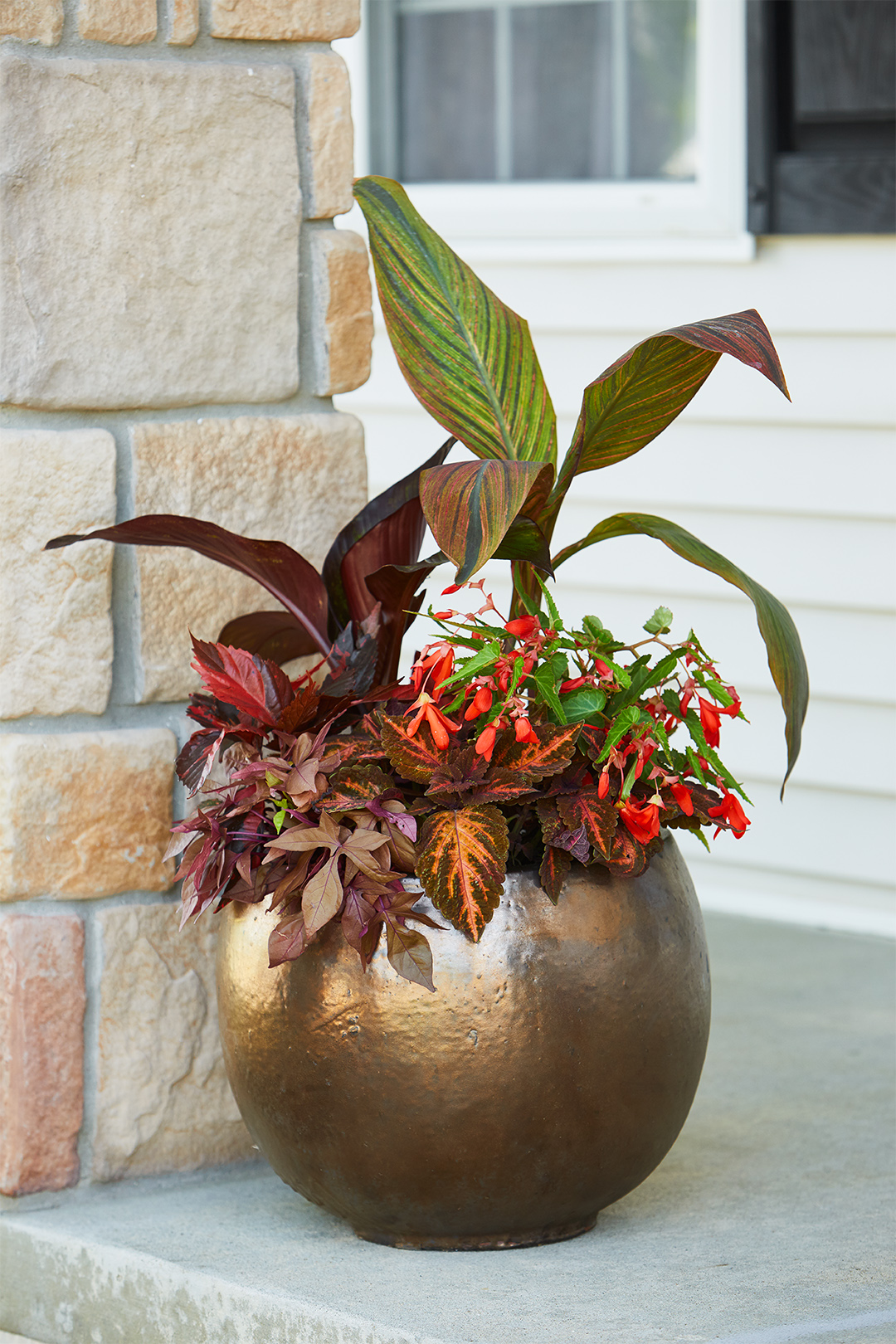 bronze pot of flowers on top porch step
