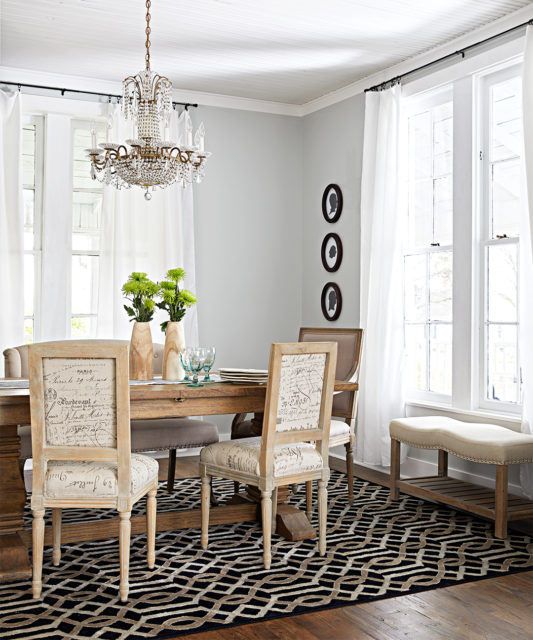 dining room room with framed silhouettes and ceiling height windows