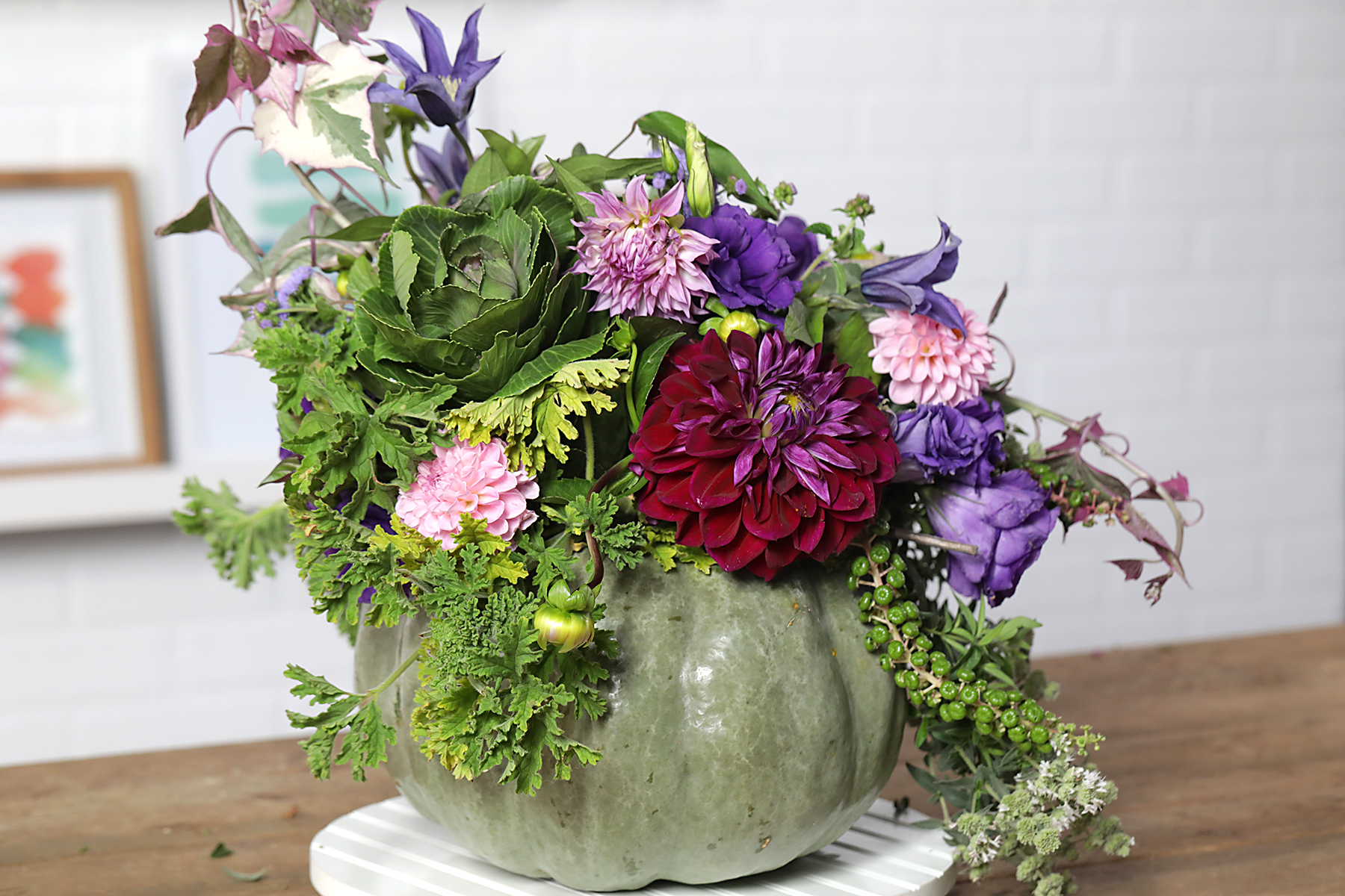 various shades of purple and pink flowers in round green pot