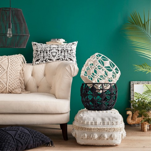 White couch and stacked baskets against a green wall