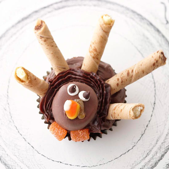 Turkey Tom Cupcakes decorated with frosting, candy, and cookies to look like a turkey