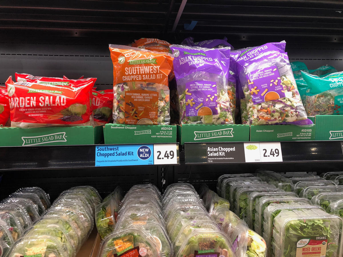 Bagged chopped salad kits in refrigerator section at Aldi grocery store