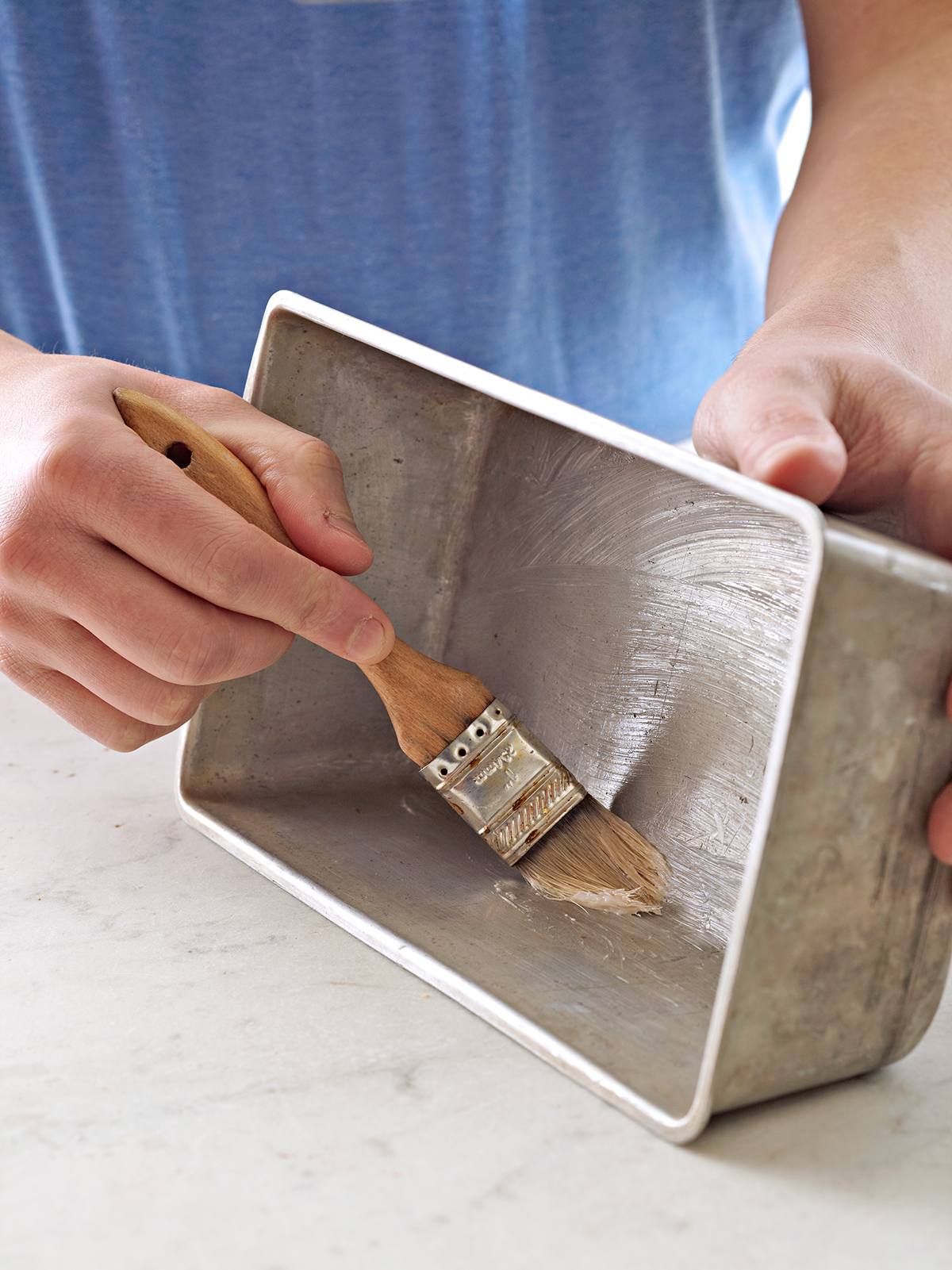 person using pastry brush to butter metal loaf pan